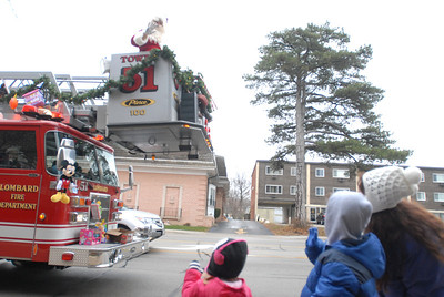 Santa Claus, riding on top of a fire truck, waves to Sharlene Ruzycki and her children, Cassidy, 2, and Michael, 6, all of Lombard, during the annual Lombard Fire Department Toy Parade along Main Street on Saturday, Dec. 8, 2012. Staff photo by Matthew Piechalak