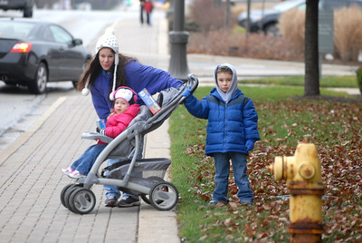 Sharlene Ruzycki and his children, Michael, 6, and Cassidy, 2, watch as Santa Claus approaches riding on top of a fire truck during the annual Lombard Fire Department Toy Parade along Main Street on Saturday, Dec. 8, 2012. Staff photo by Matthew Piechalak