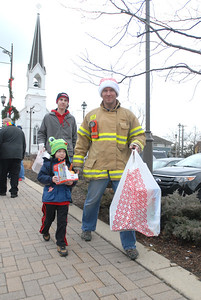 Lombard firefighter/paramedic Dale Farris and his son, Zayo, 4, carry donated toys back to the fire truck during the annual Lombard Fire Department Toy Parade along Main Street on Saturday, Dec. 8, 2012. Staff photo by Matthew Piechalak