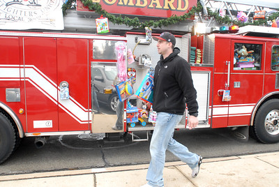 Glenbard East baseball coach Joel Pelland carries a donated toy back to the fire truck during the annual Lombard Fire Department Toy Parade along Main Street on Saturday, Dec. 8, 2012. Staff photo by Matthew Piechalak