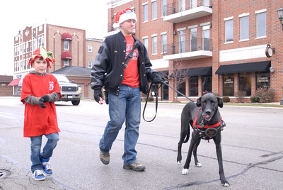 Lombard firefighter/paramedic Chris Brasile and his son, Owen, 8, walk with their dog, Reese, during the annual Lombard Fire Department Toy Parade along Main Street on Saturday, Dec. 8, 2012. Staff photo by Matthew Piechalak