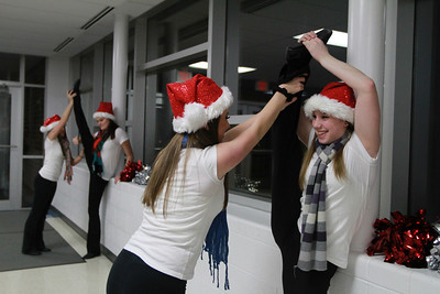 Hannah Andrzejewski (left) helps out Julieanne Haas stretch before they perform on Friday, Dec. 14. Sarah Minor — sminor@shawmedia.com