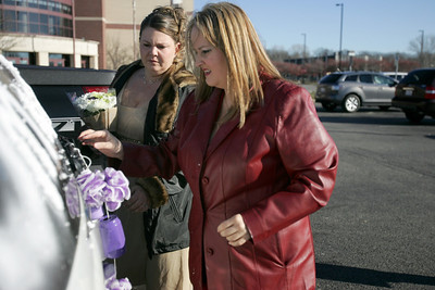 Monica Maschak - mmaschak@shawmedia.com Bride Trisha Brock (left) helps her friend Roxanne Diaz hang wedding car cans to the back of the newlywed's car after Brock married her groom Jesus Deleno at the McHenry County Court House on Wednesday, December 12, 2012.