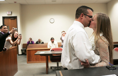 Monica Maschak - mmaschak@shawmedia.com Family and friends snap a photo of Ambrocio and Amy Avitia sharing their first kiss as husband and wife at the McHenry Couty Court House on Wednesday, December 12, 2012.  The couple has known each other for 17 years and had been dating for four months when they made the appointment this past Monday to wed on the last repetitive date of the century.