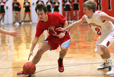 Monica Maschak - mmaschak@shawmedia.com Marian Central's Matt Yuk dribbles down the court as he is pressured by McHenry's defense on either side in a game at McHenry High School on December 6, 2012.  The Warriors defeated the Hurricanes 71-48.