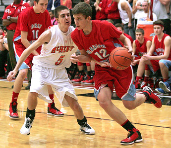 Monica Maschak - mmaschak@shawmedia.com Marian Central's Casey Einecker avoids a defender as he moves closer to the hoop in a game at McHenry High School on December 6, 2012.  The Warriors defeated the Hurricanes 71-48.
