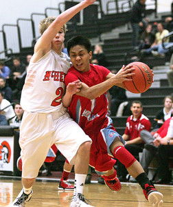 Monica Maschak - mmaschak@shawmedia.com Marian Central's Derreck Caldez collides with a defender as he moves closer to the hoop in a game at McHenry High School on December 6, 2012.  The Warriors defeated the Hurricanes 71-48.