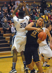 Hinsdale South's Barret Benson pulls in the rebound after blocking Tyler Pearson's shot. Downers Grove South wins a close varsity boys basketball game, 63-57, at home against Hinsdale South on Friday, Dec. 7, 2012. Staff photo by Bill Ackerman