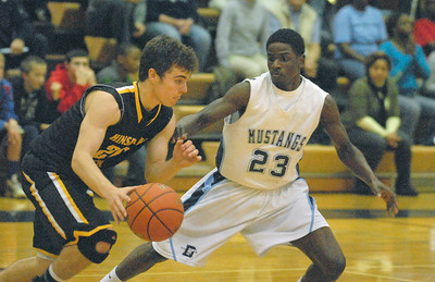 Hinsdale South's D.J. Deolitsis brings the ball down court with Downers Grove South's Paul Engo III (#23) guarding him. The Mustangs win a close varsity boys basketball game, 63-57, at home on Friday, Dec. 7, 2012. Staff photo by Bill Ackerman