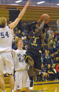 Hinsdale South's Marcel Phillips shoots over Downers Grove South's Robert Mara (#54) in Downers Grove on Friday, Dec. 7, 2012. Staff photo by Bill Ackerman