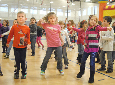 """James Benson (from left), 4; Brooke Coffman, 5; and Cailin Kwasneski, 5; all of Lemont, freeze dance while a DJ plays music and then freeze when the music stops. The Lemont Park District starts the new year, twelve hours early, with its """"Happy New Year Family Fun Day"""" with games, crafts, and a balloon drop at the stroke of noon on Monday, Dec. 31, 2012. Bill Ackerman — backerman@shawmedia.com"""