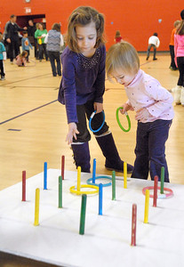 """Bonnie Schuch, 5, of Lemont, and her sister, Bridget, 2, take their own approach to ring toss. The Lemont Park District starts the new year, twelve hours early, with its """"Happy New Year Family Fun Day"""" with games, crafts, and a balloon drop at the stroke of noon on Monday, Dec. 31, 2012. Bill Ackerman — backerman@shawmedia.com"""
