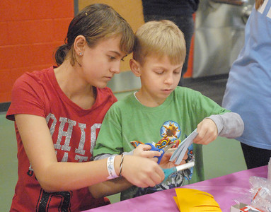 """Cassandra Stec, 13, of Lemont, helps her brother, Brandon, 6, cut the slots in a paper lantern. The Lemont Park District starts the new year, twelve hours early, with its """"Happy New Year Family Fun Day"""" with games, crafts, and a balloon drop at the stroke of noon on Monday, Dec. 31, 2012. Bill Ackerman — backerman@shawmedia.com"""
