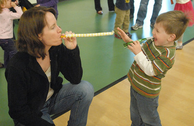 """Charlie Brandt, 2-1/2, of Lemont, laughs in delight as his mom, Julie, blows one of the party favors passed out at the Lemont Park District's """"Happy New Year Family Fun Day"""" on Monday, Dec. 31, 2012. Bill Ackerman — backerman@shawmedia.com"""