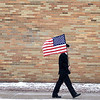 West Aurora High School sophomore Kien Huynh carries a flag as he exits the school to join other students and faculty members of West Aurora High School, along with community members, to pay tribute to Spc. Christopher Patterson as the hearse carrying his body passes the school Friday morning.  Patterson, a member of the Indiana National Guard, died while serving in Afghanistan Jan. 6. <br /> 1/20/2012(Sandy Bressner photo)