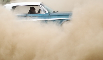 Josh Peckler - Jpeckler@shawmedia.com The driver and his car can barely be seen as it picks up dust during a car stunt show for the Iron Invasion Festival at the Mchenry County Fair Grounds in Woodstock.