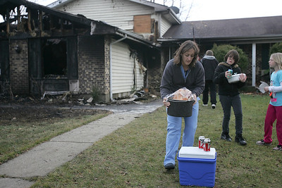 Monica Maschak - mmaschak@shawmedia.com Stacy Larzelere carries a turkey out of her ex-husband's burned home on Thanksgiving day.  A fire broke out in the Crystal Lake home in the 700 block of Windsor Drive after a deep fryer ignited the garage.