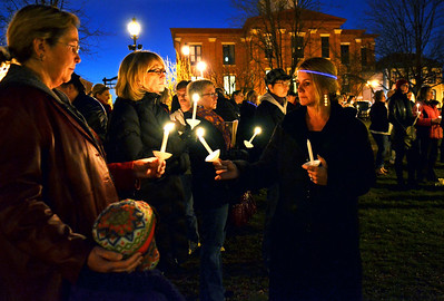 Monica Maschak - mmaschak@shawmedia.com McHenry County crisis worker Holly (right) lights the candles of those, whose lives have been touched by suicide, gathered at the Woodstock Square for a remembrance program in response to the disturbing increase in suicides in the area.