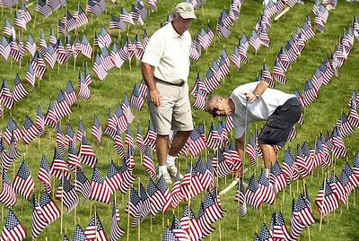 H. Rick Bamman -hbamman@shawmedia.com Sun City of Huntley residents Bob Wold (left) and Chuck Czochara plant flags September 7, 2012 for the 9/11 American Flag Memorial.