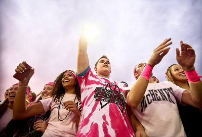 Josh Peckler - Jpeckler@shawmedia.com Wearing pink attire McHenry High School students from left (Josie Hobbs, Trevor Folz and Shane Varil cheer on McHenry as they enter the field to play against Dundee-Crown High School at Mchenry High Schoo. Mchenry High School held a Pink-Out Play For a Cure Week to bring awareness to cancer in women.