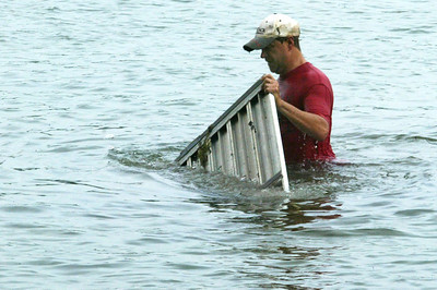 H. Rick Bamman -hbamman@shawmedia.com Larry Galizi wades in Crystal Lake morning to recover submerged pieces of a pier that was blown apart by high winds.