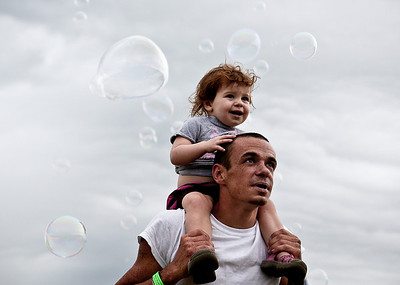 Josh Peckler - Jpeckler@shawmedia.com Bobby Rosenthal of Mchenry holds his daughter Tru, 2 on his shoulders as bubbles fly by during The Lake in the Hills Summer Sunset Festival at Sunset Park.