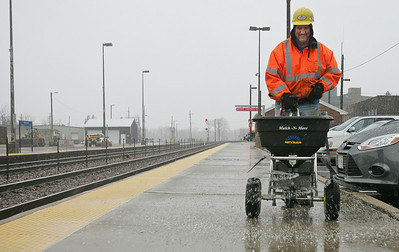 Monica Maschak - mmaschak@shawmedia.com Garry Bomkamp, with Union Pacific Railroads, salts the walkways of the Harvard Metra Station as the Winter Storm Warning began to take effect promptly at 3 p.m. on Thursday, December 20, 2012.