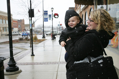 Monica Maschak - mmaschak@shawmedia.com Jen Sanders holds up her 18-month-old son Jordan Marks to witness his first real snow fall in downtown Harvard Thursday afternoon.
