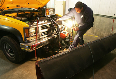 H. Rick Bamman - hbamman@shawmedia.com Lake In The Hills public works maintenance mechanic apprentice Tony Vildales (cq) repairs a hydraulic lift fo a snow plow Thursday in preparation of the winter storm. LITH will have 20 plows out during a shift and has 300 tons of salt stockpiled according to Manny Gomez Deputy Public Works Director.