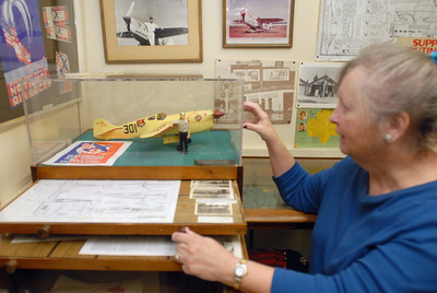 Volunteer Susan Donahue points to a model of pilot Rudy Kling at the Lemont Historical Society, 306 Lemont St. on Tuesday, Dec. 4, 2012. Kling, a Lemont native who died 75 years ago on Dec. 3, gained national fame when his won the Thompson Trophy at the Cleveland Air Races in 1937. Staff photo by Matthew Piechalak