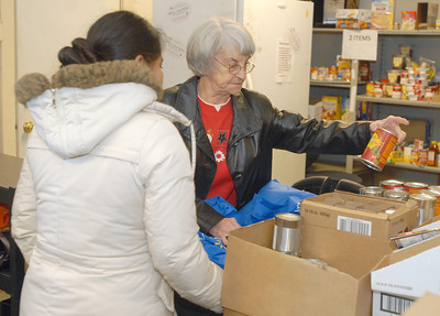 On Saturday, Dec. 22, 2012, Shirley Swanson (right), of West Chicago, assists a guest at the Neighborhood Food Pantries site in West Chicago, located behind the Crossroads Restoration Church. Bill Ackerman — backerman@shawmedia.com