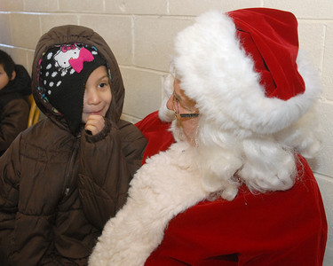 Isabella Castro, 6, of West Chicago takes a seat with Santa, putting in a special appearance at the Neighborhood Food Pantries site in West Chicago, located behind the Crossroads Restoration Church on Saturday, Dec. 22, 2012. Santa, aka Loren Bustin, of Wheaton, is an elder of the church. Bill Ackerman — backerman@shawmedia.com