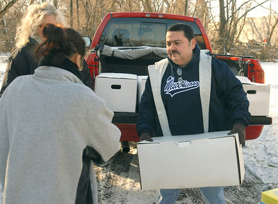 West Chicago Mayor Ruben Pineda carries a complete ham dinner for a guest at the Neighborhood Food Pantries site in West Chicago, located behind the Crossroads Restoration Church on Saturday, Dec. 22, 2012. Bill Ackerman — backerman@shawmedia.com