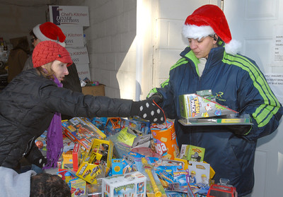 Volunteers Laura Grodoski (left) and lead elf Ivelisse Rodriguez, both of West Chicago, add a Jenga game to some other age-appropriate toys for guests on Saturday, Dec. 22, 2012. Santa puts in a special appearance at the Neighborhood Food Pantries site in West Chicago, located behind the Crossroads Restoration Church. Bill Ackerman — backerman@shawmedia.com