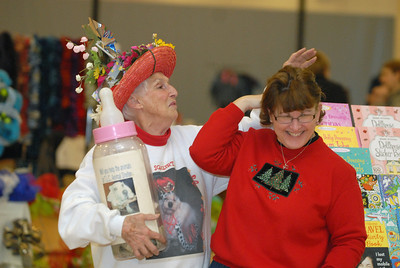 "Annie Coleman, left, of Lemont, messes around with Judy Konkel, of Lockport, before taking a posed picture at Lemont Park District's annual ""Shop Til You Drop"" event at The CORE Fitness & Aquatic Complex, 16028 127th St. in Lemont on Saturday, Dec. 8, 2012. Coleman was collecting donations for the Tender Loving Care Animal Shelter in Homer Glen. Staff photo by Matthew Piechalak"
