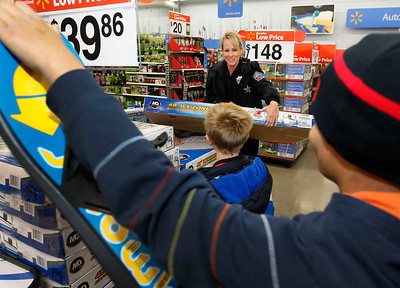 Candace H. Johnson – For the Northwest Herald Brandy Wenrich, a police officer with the Johnsburg Police Department, helps Zachary, 8, and Spencer, 11, both of Johnsburg, pick out some toys including an air-powered hockey table during Shop with a Cop at the Walmart in Johnsburg. The event was sponsored by the McHenry County Police Charities.