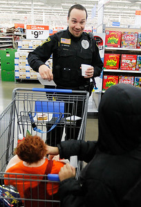 Candace H. Johnson – For the Northwest Herald George Anderson, a Spring Grove police officer, talks with Justice, 6, of Spring Grove, while shopping for toys with him during Shop with a Cop at the Walmart in Johnsburg. The event was sponsored by the McHenry County Police Charities.