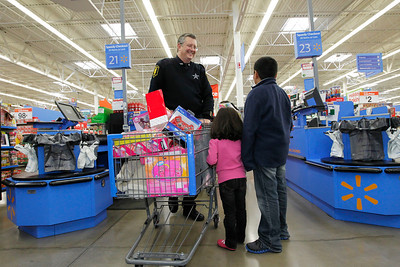 Candace H. Johnson – For the Northwest Herald Bob Schultz, a Harvard police officer, talks with Marina, 5, and her brother, Saul, 10, both of Harvard, while they wait on line to check out during Shop with a Cop at the Walmart in Johnsburg. The event was sponsored by the McHenry County Police Charities.