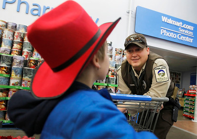 Candace H. Johnson – For the Northwest Herald Chris, 7, of Big Foot Prairie, wears his brand new cowboy hat while talking with Corey Burley, a police officer with the McHenry County Conservation District, during Shop with a Cop at the Walmart in Johnsburg. The event was sponsored by the McHenry County Police Charities.