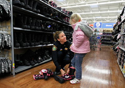 Candace H. Johnson – For the Northwest Herald Laura King, commander with the City of McHenry Police Department, helps Terrah, 5, of McHenry with trying on Hello Kitty winter boots during Shop with a Cop at the Walmart in Johnsburg. The event was sponsored by the McHenry County Police Charities.