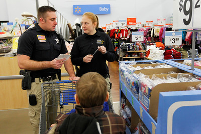 Candace H. Johnson – For the Northwest Herald Daniel Kramer and Caitlynn Kelly, both deputy sheriffs with McHenry County, compare their shopping lists while Austin, 9, and Daniel, 6, both of Harvard, stay close to them during Shop with a Cop at the Walmart in Johnsburg. The event was sponsored by the McHenry County Police Charities.