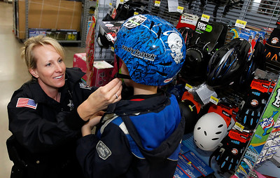 Candace H. Johnson – For the Northwest Herald Brandy Wenrich, a police officer with the Johnsburg Police Department, helps Zachary, 8, of Johnsburg try on a bike helmet during Shop with a Cop at the Walmart in Johnsburg. The event was sponsored by the McHenry County Police Charities.