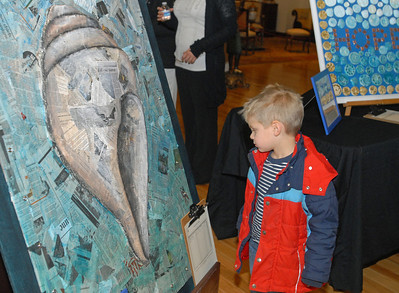 Hugh Ascher, 4, of Clarendon Hills, gets a closer look at a collage of newspaper stories about Hurricane Sandy, created by fourth graders at Walker School, in Clarendon Hills. On Wednesday, Dec. 12, 2012, the Art & Antique Centre of Oak Brook hosts a silent auction of seashell-inspired art by area students, as a part of a larger fundraising effort for victims of Hurricane Sandy. Staff photo by Bill Ackerman