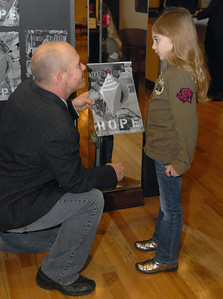 Mike Divelbiss, the art teacher for Butler School District 53, talks with Nicole Counter, 7, a second grader at Brook Forest Elementary School, about the conch contour collage she created. On Wednesday, Dec. 12, 2012, the Art & Antique Centre of Oak Brook hosts a silent auction of seashell-inspired art by area students, as a part of a larger fundraising effort for victims of Hurricane Sandy. Staff photo by Bill Ackerman