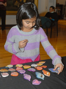 Imaan Zaheer, 8, a second grader at Brook Forest Elementary School, arranges shell magnets designed by students at Monroe Elementary School in Hinsdale. On Wednesday, Dec. 12, 2012, the Art & Antique Centre of Oak Brook hosts a silent auction of seashell-inspired art by area students, as a part of a larger fundraising effort for victims of Hurricane Sandy. Staff photo by Bill Ackerman