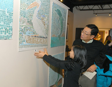 Jasmine Tan, 9, a fourth grader at Brook Forest Elementary School, shows her dad, Kevin, a mosaic that she and classmates created. The Tans are from Oak Brook. On Wednesday, Dec. 12, 2012, the Art & Antique Centre of Oak Brook hosts a silent auction of seashell-inspired art by area students, as a part of a larger fundraising effort for victims of Hurricane Sandy. Staff photo by Bill Ackerman
