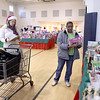 "Donna Patton of Batavia (right) chooses toys and books for her daughter with the help of volunteer ""elf"" Lisa Scott of Bartlett during the Toy Shop distribution day at the Salvation Army's Joe K. Anderson Community Center in St. Charles Wednesday morning.(Sandy Bressner photo)"