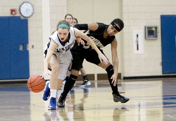 Geneva's Morgan Seberger (left) gets past Streamwood's Deja Moore to grab a loose ball during their game at Geneva Wednesday night.(Sandy Bressner photo)