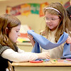 Heartland Elementary School fourth-grader Leah Davine (left) and kindergartner Abby Arnold make scarves at the Geneva school Wednesday afternoon. The scarves will be donated to Marianjoy Rehabilitation Hospital in Wheaton.(Sandy Bressner photo)