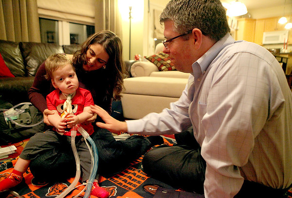William Whiston, 17 months, with his parents, Melanie and Dan, in their Geneva home. William was born with myotubular myopothy, a rare genetic disorder that does not allow him to move his muscles with any force.(Sandy Bressner photo)